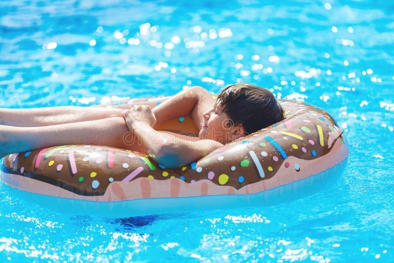 Adolescente bonito feliz do rapaz pequeno que encontra-se em um anel inflável da filhós na piscina Jogos ativos na água, férias,  imagem de stock royalty free