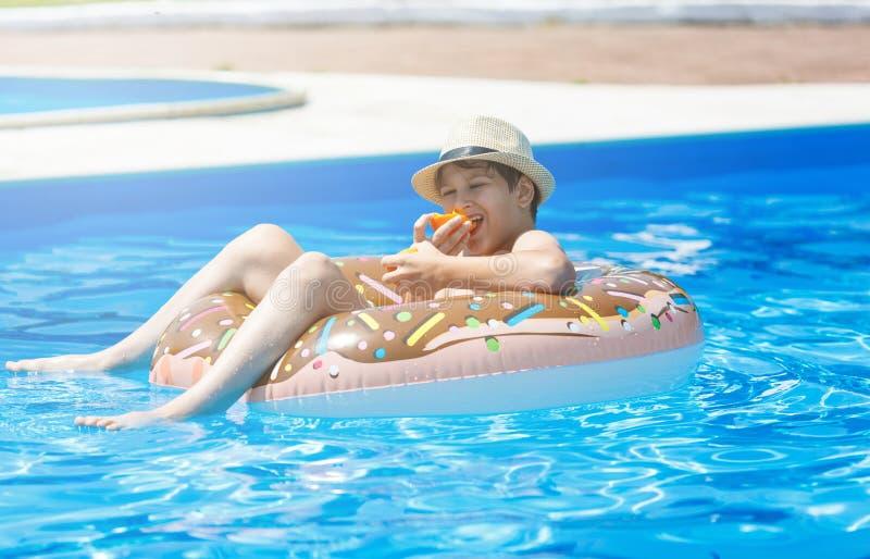 Adolescente bonito feliz do rapaz pequeno que encontra-se em um anel inflável da filhós na piscina Jogos ativos na água, férias,  imagens de stock royalty free