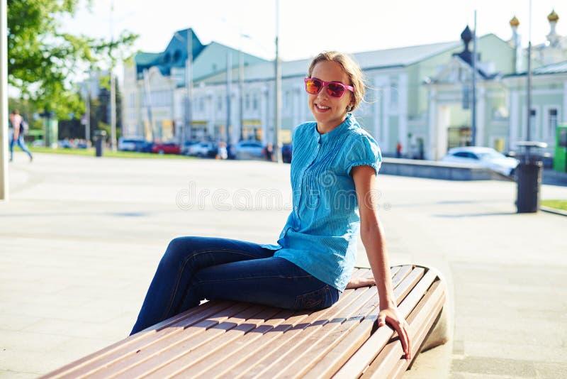 Adolescente bonito na roupa ocasional e nos óculos de sol que sentam-se sobre fotografia de stock royalty free