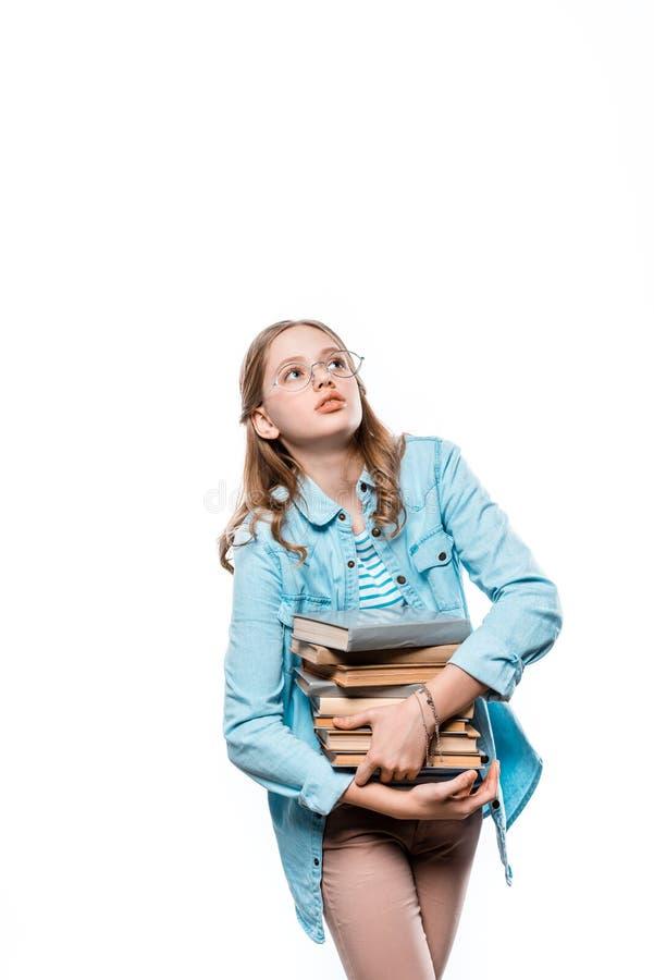 Adolescente bonito nos monóculos que guardam a pilha de livros e que olham acima imagens de stock