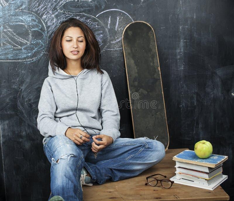 Adolescente bonito novo na sala de aula no assento do quadro-negro na tabela que sorri, conceito moderno do moderno do aluno, est fotografia de stock royalty free