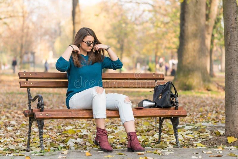 Adolescente bonito novo que senta-se no banco de parque e que guarda seu cabelo imagem de stock