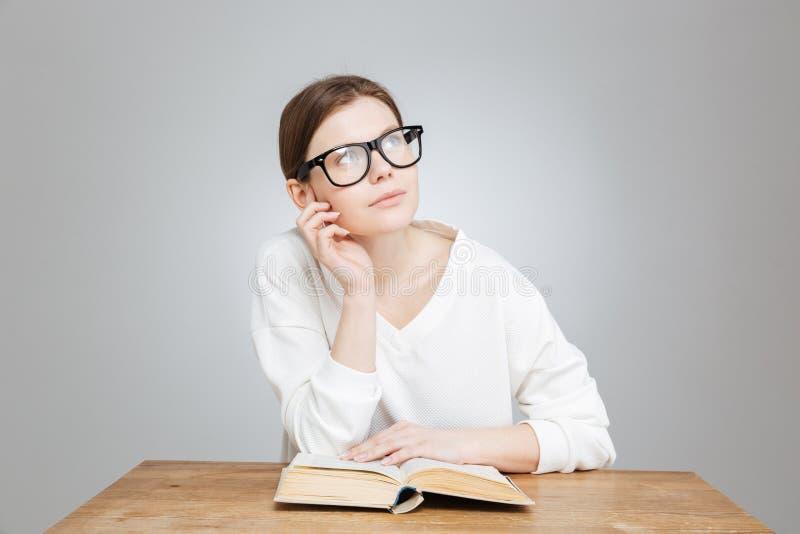 Adolescente bonito pensativo no livro e no pensamento de leitura dos vidros fotografia de stock royalty free