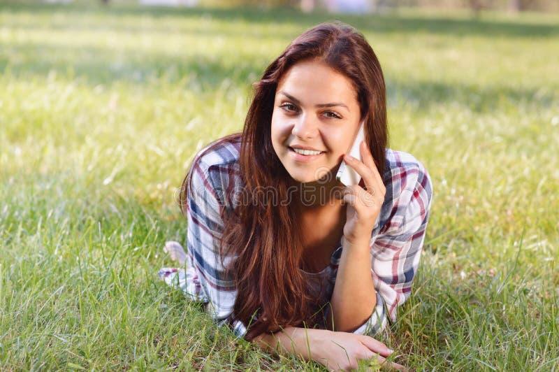 Adolescente bonito que encontra-se no campo da grama verde e da conversa pelo telefone fotos de stock royalty free