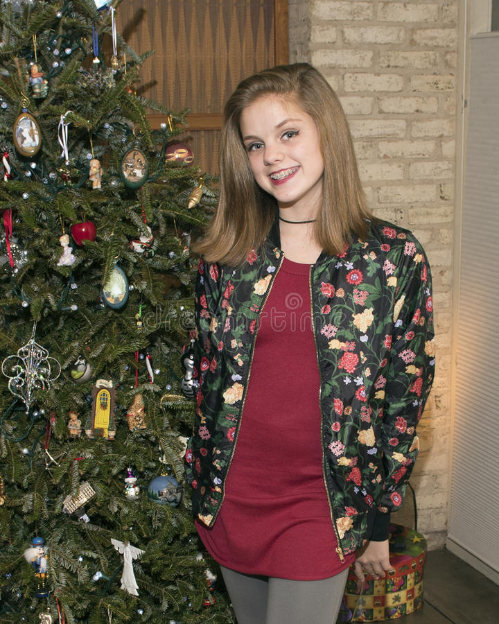 Adolescente bonito que está na frente de uma árvore de Natal fotos de stock royalty free