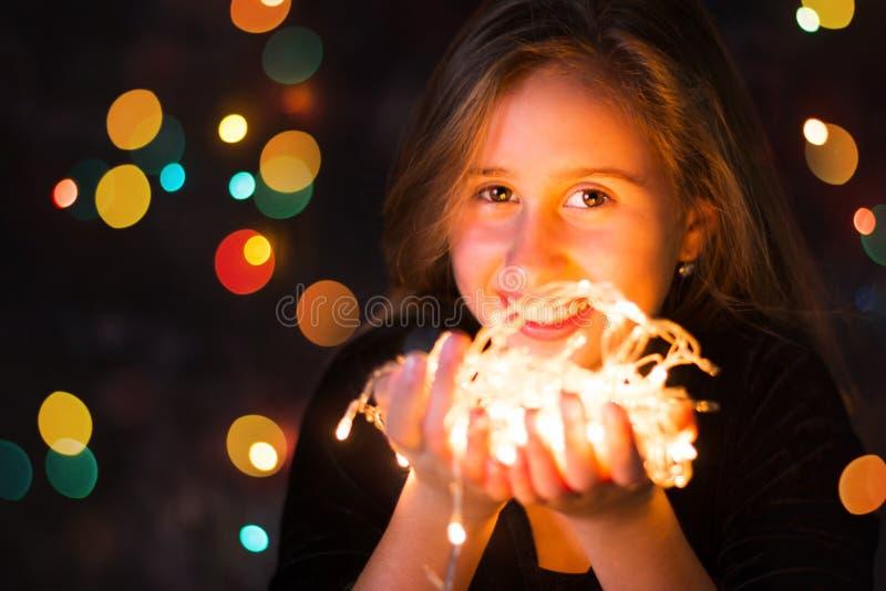 Adolescente bonito que guarda luzes festivas fotografia de stock