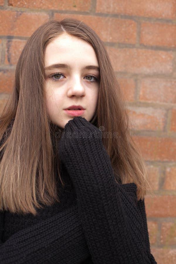 Adolescente bonito que huddling em sua ligação em ponte imagens de stock royalty free