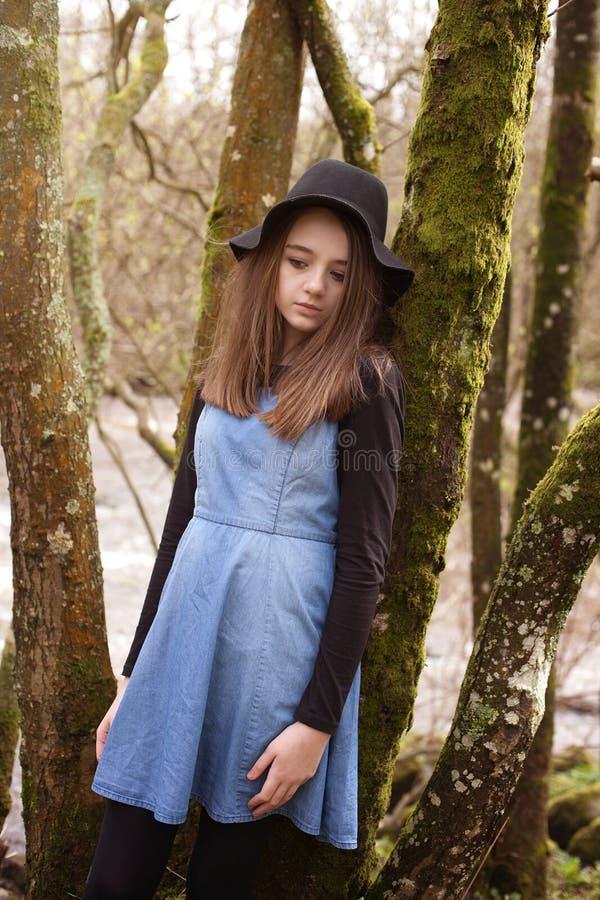 Adolescente bonito que inclina-se contra uma árvore com um rio atrás fotografia de stock royalty free