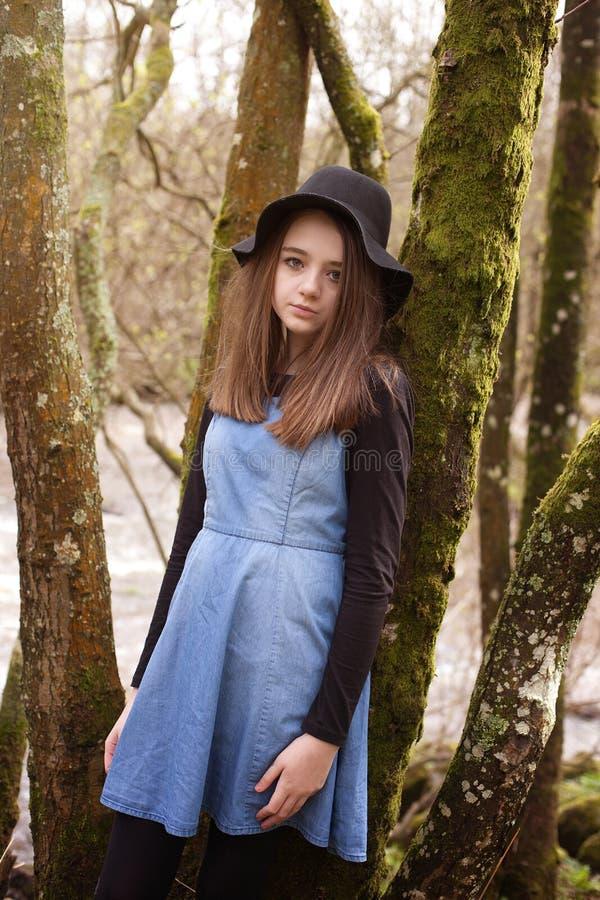 Adolescente bonito que inclina-se contra uma árvore com um rio no b foto de stock royalty free