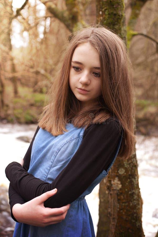 Adolescente bonito que inclina-se contra uma árvore que olha triste imagem de stock royalty free