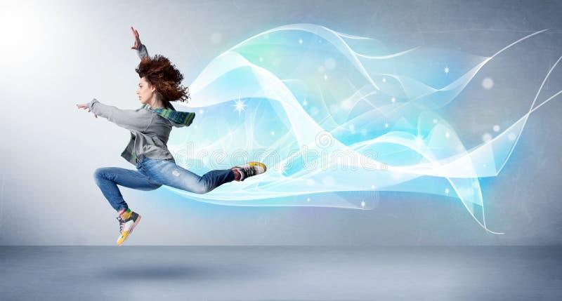 Adolescente bonito que salta com o lenço azul abstrato em torno dela imagem de stock royalty free