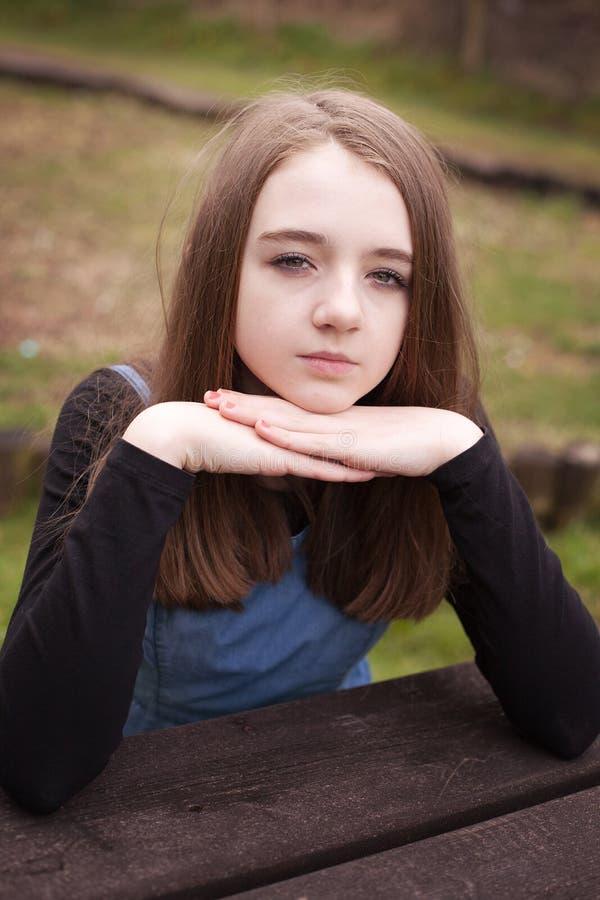 Adolescente bonito que senta-se fora em uma tabela de piquenique fotografia de stock royalty free