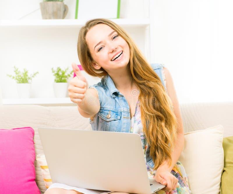 Adolescente bonito que senta-se no sofá em casa com seu portátil fotografia de stock