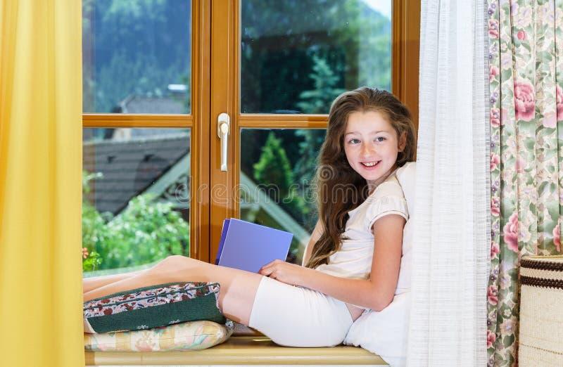 Adolescente bonito que siiting no siil da janela imagens de stock