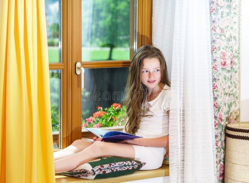 Adolescente bonito que siiting no siil da janela fotos de stock
