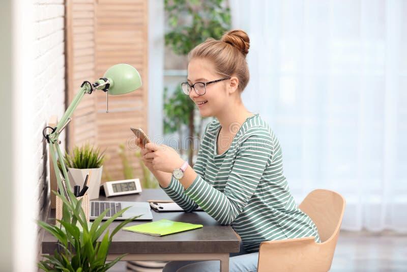 Adolescente bonito que usa o telefone celular na tabela imagem de stock royalty free