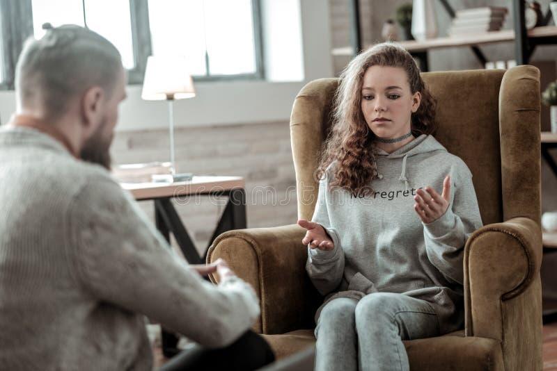 Adolescente bonito que veste o hoodie cinzento que visita o conselheiro privado imagens de stock