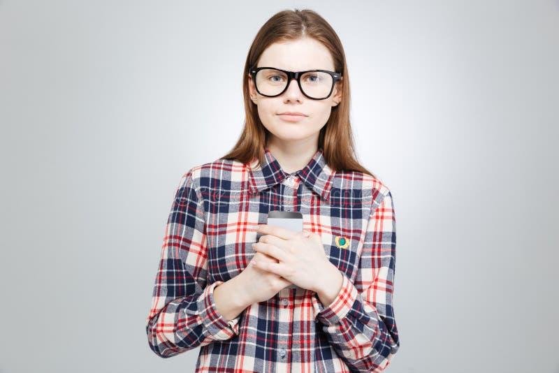 Adolescente bonito sério nos vidros que snading e que guardam o smartphone fotografia de stock royalty free