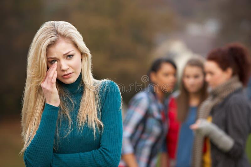 Adolescente bouleversée avec le bavardage d'amis photos stock