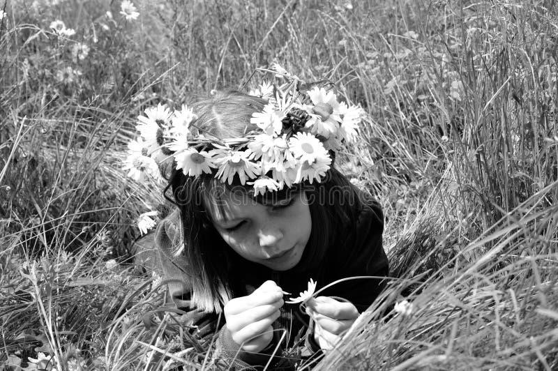 Adolescente branco que conta as pétalas na grama fotografia de stock