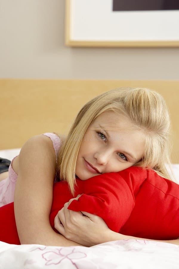 Adolescente in camera da letto che abbraccia cuscino immagine stock