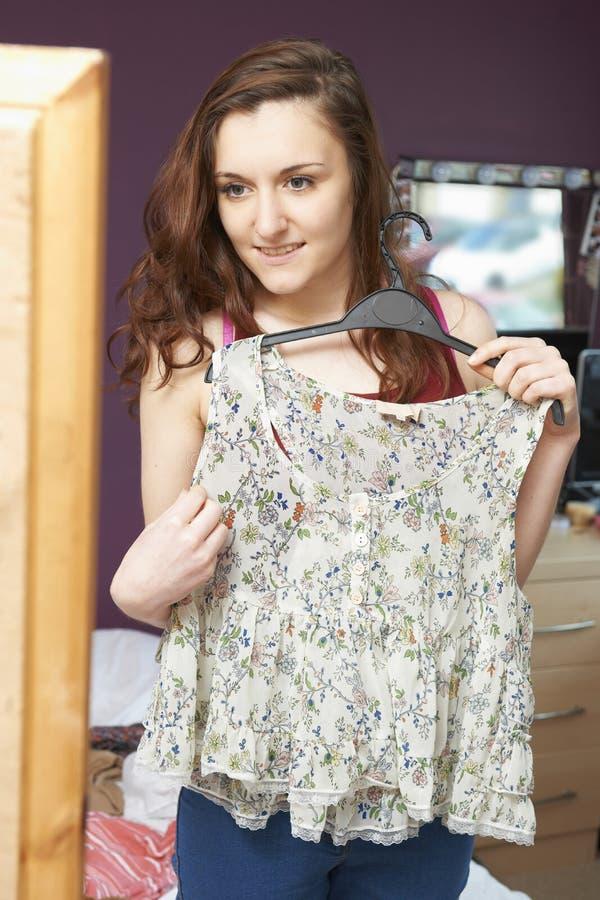 Adolescente in camera da letto che sceglie i vestiti per durare fotografie stock