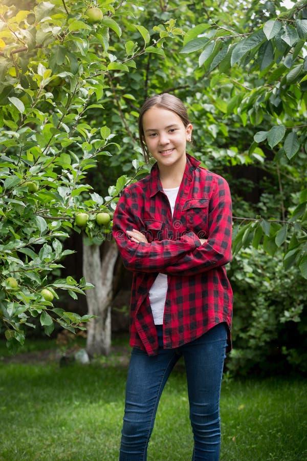 Adolescente in camicia a quadretti rossa che posa al giardino della mela fotografia stock libera da diritti