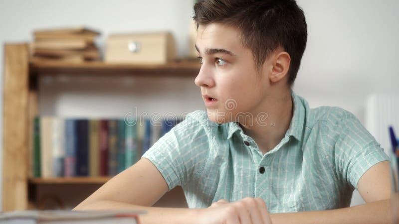 Adolescente cansado de fazer lições, pensando fotografia de stock