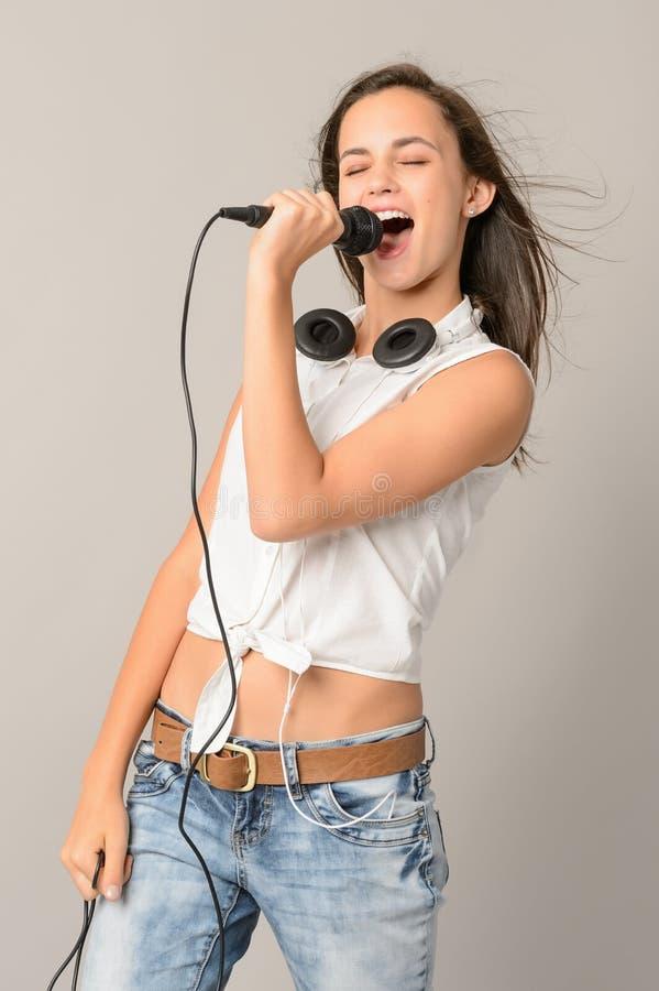 Adolescente cantante con los ojos cerrados micrófono imagenes de archivo