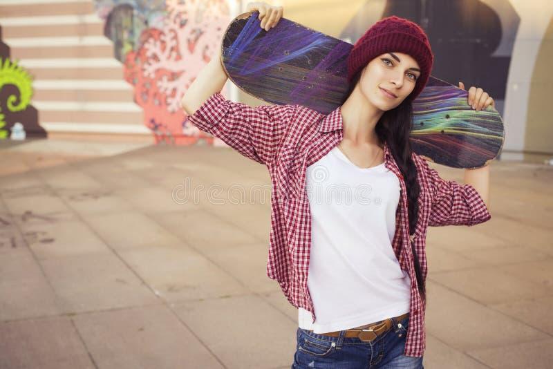 Adolescente castana in attrezzatura dei pantaloni a vita bassa (jeans mettono, keds, camicia di plaid, cappello) con un pattino a fotografia stock