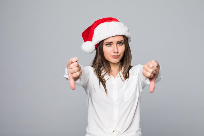 Adolescente caucasiano triste bonito que vestem o chapéu de Santa e luvas que mostram os polegares para baixo e que fazem a expre imagens de stock royalty free