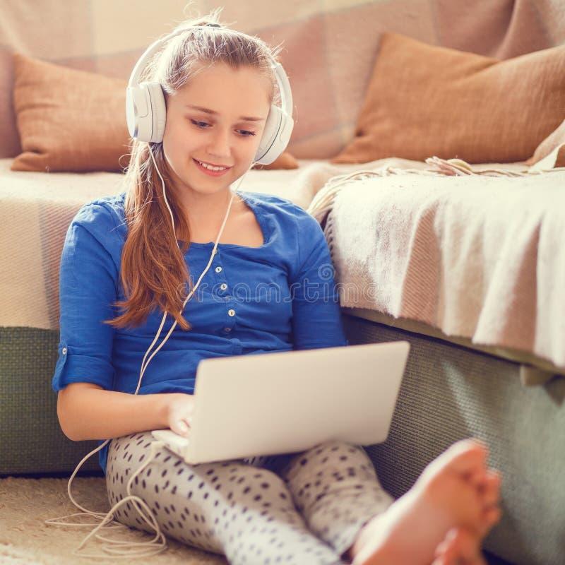 Adolescente caucasico divertendosi facendo uso del computer portatile fotografia stock