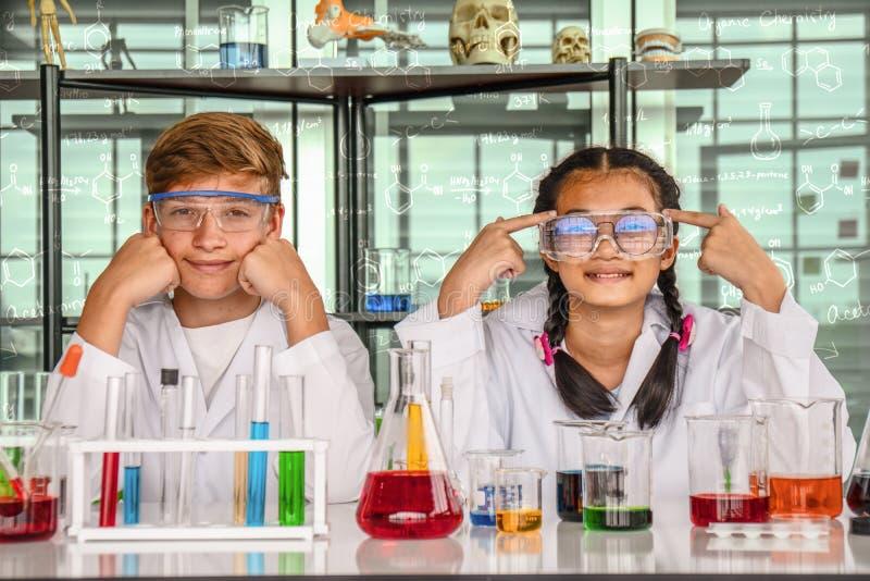 Adolescente caucasico e adolescente asiatico in laboratorio con la provetta fotografia stock