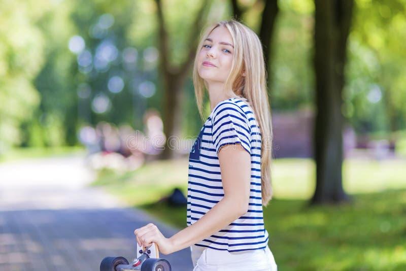 Adolescente caucasienne de sourire heureuse posant avec la longue planche à roulettes dehors photos stock