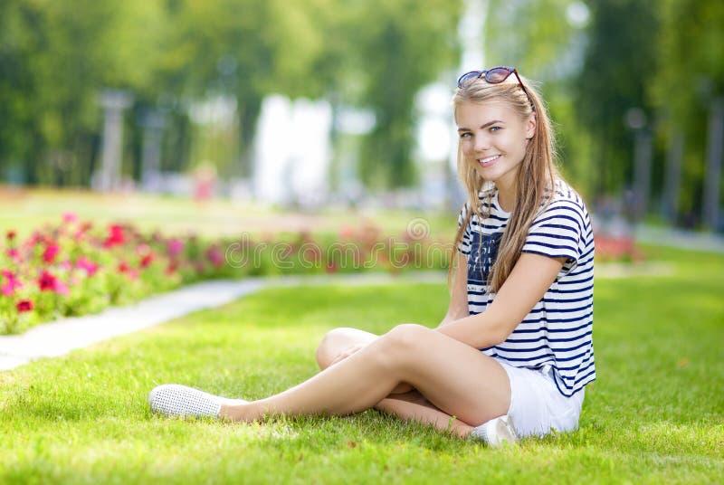 Adolescente caucasienne de sourire heureuse posant sur l'herbe en parc fleuri vert d'été images stock