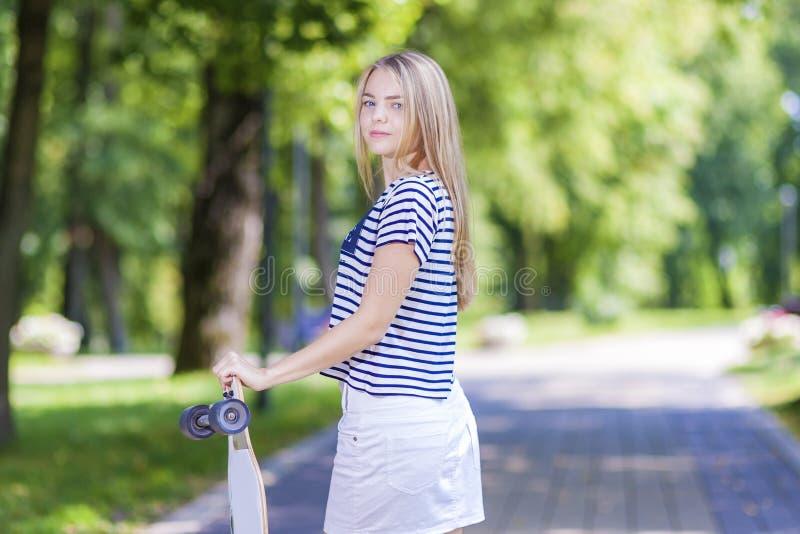 Adolescente caucasienne posant avec la longue planche à roulettes dans la forêt verte photos stock