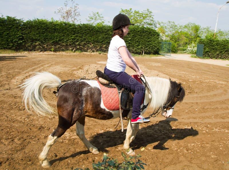 Adolescente a cavallo che indossa casco fotografia stock libera da diritti