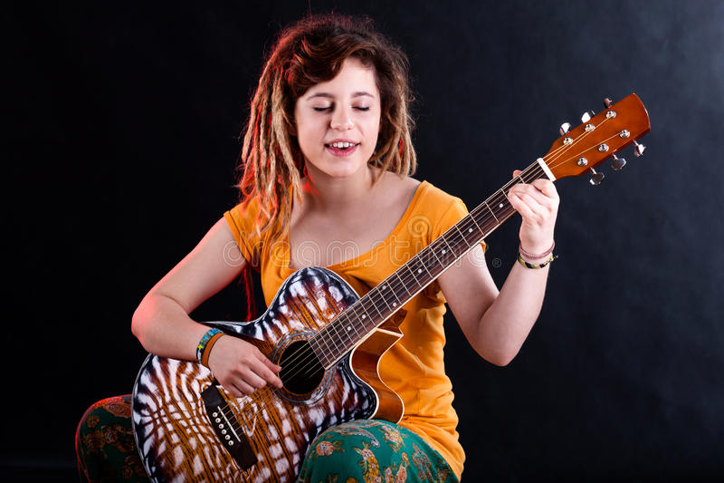 Adolescente chantant et jouant la guitare image stock