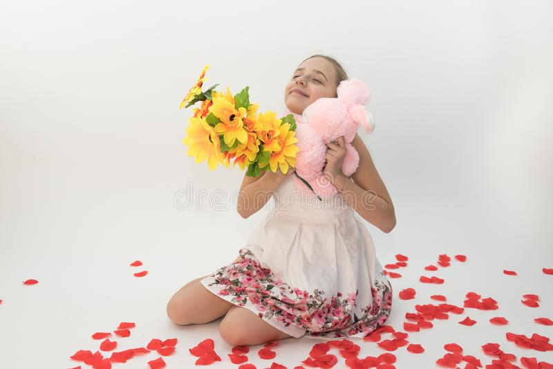 Adolescente che abbraccia un regalo di giorno del ` s del biglietto di S. Valentino e un mazzo di fiori fotografia stock libera da diritti