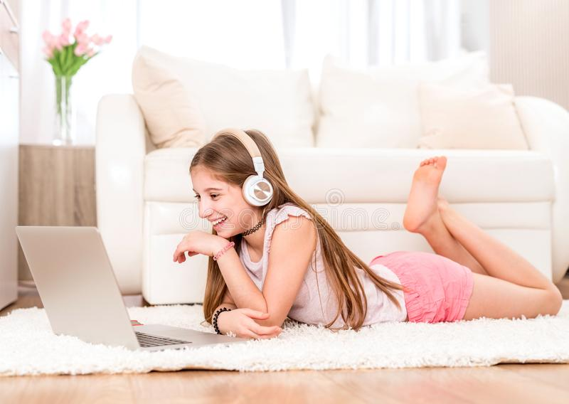 Adolescente che ascolta la musica al suo computer portatile immagini stock