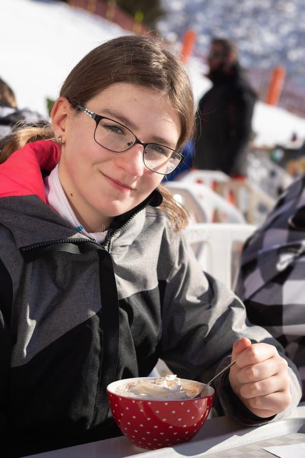 Adolescente che beve una ciotola di bevanda della cioccolata calda con panna montata in montagne Un ristorante disposto su un pen immagine stock