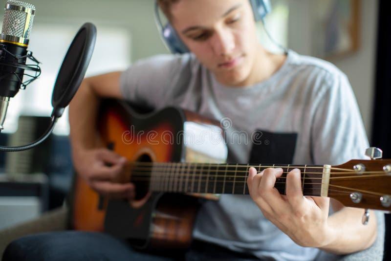 Adolescente che gioca chitarra e che registra musica a casa immagini stock libere da diritti