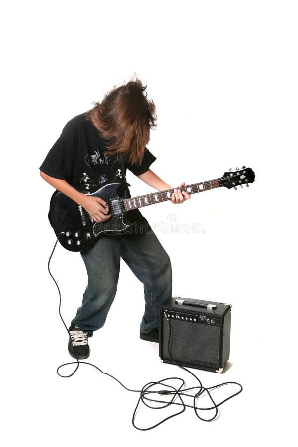 Adolescente che gioca chitarra elettrica con l'amplificatore immagini stock