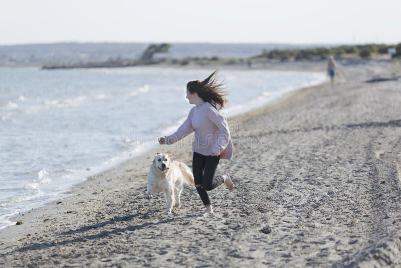 Adolescente che gioca con il suo cane su una spiaggia fotografia stock
