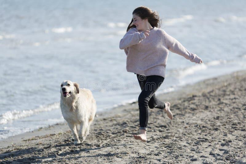 Adolescente che gioca con il suo cane su una spiaggia immagine stock libera da diritti