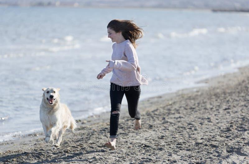 Adolescente che gioca con il suo cane su una spiaggia fotografie stock