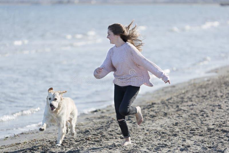 Adolescente che gioca con il suo cane su una spiaggia fotografia stock libera da diritti