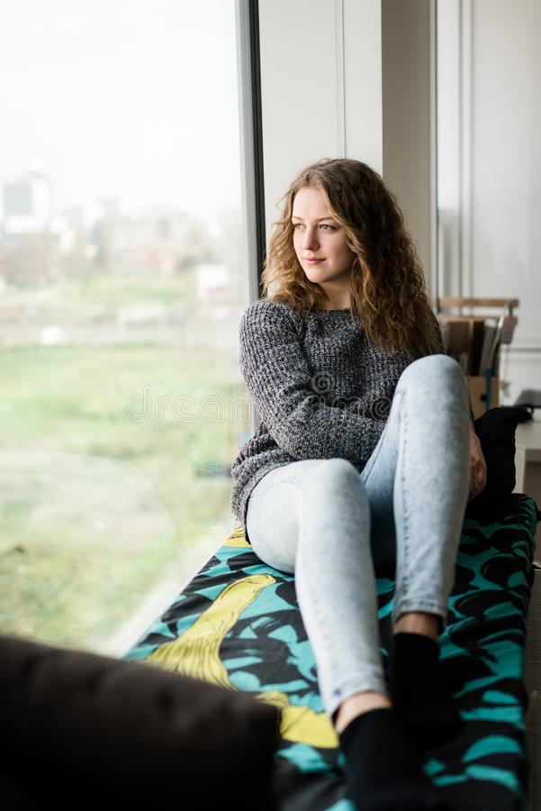 Adolescente che guarda attraverso la finestra fotografie stock