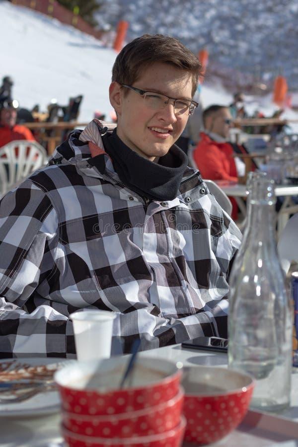 Adolescente che ha una rottura da corsa con gli sci in un ristorante della montagna disposto su un pendio dello sci fotografia stock