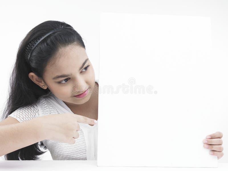Download Adolescente Che Indica Alla Sua Scheda Fotografia Stock - Immagine di bello, blank: 7320264